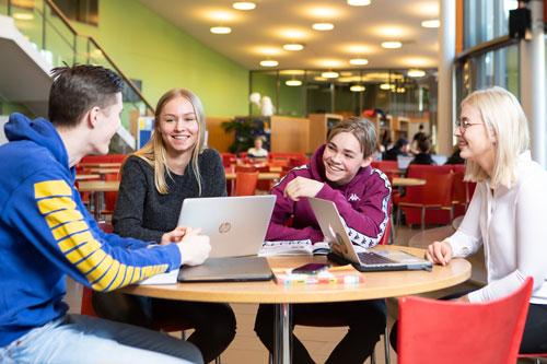 Opiskelijoita pöydän ääressä.