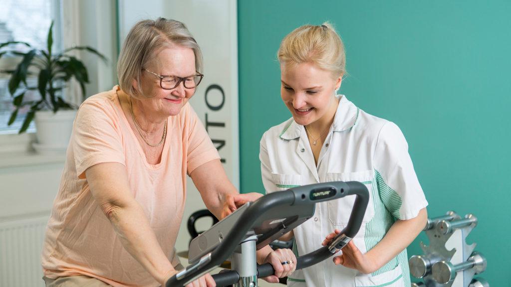 Hoitaja ja ikäihminen tutustuvat kuntopyörän käyttöön