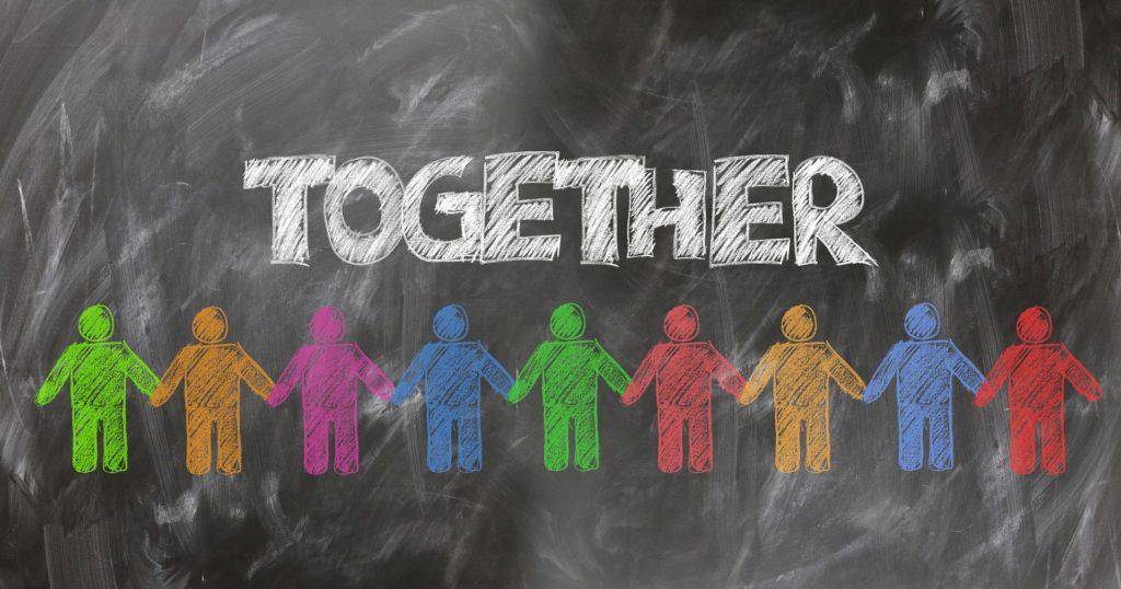 Liitutaululle on kirjoitettu Together (yhdessä) ja piirretty ihmishahmoja